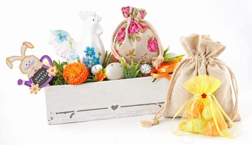 Bunte Osterkomposition aus Stoffbeuteln und einem rechteckigen Blumentopf mit gefärbten Ostereiern
