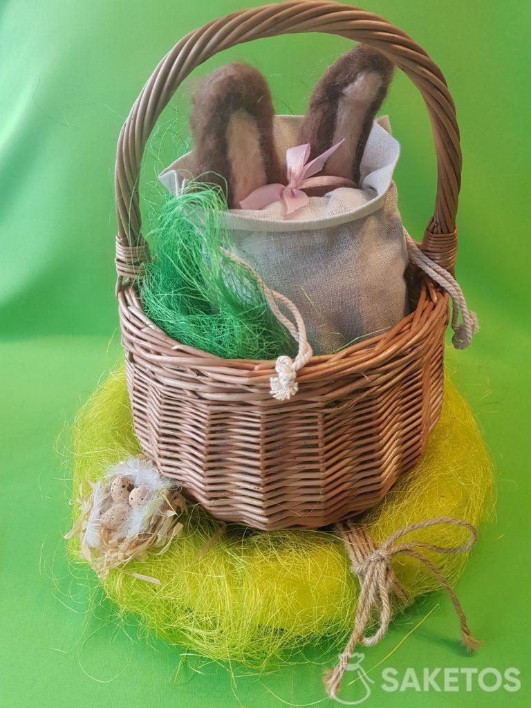 Korb mit einem Leinenbeutel, aus dem die Ohren eines Filzhasen aus Kammwolle herausragen.