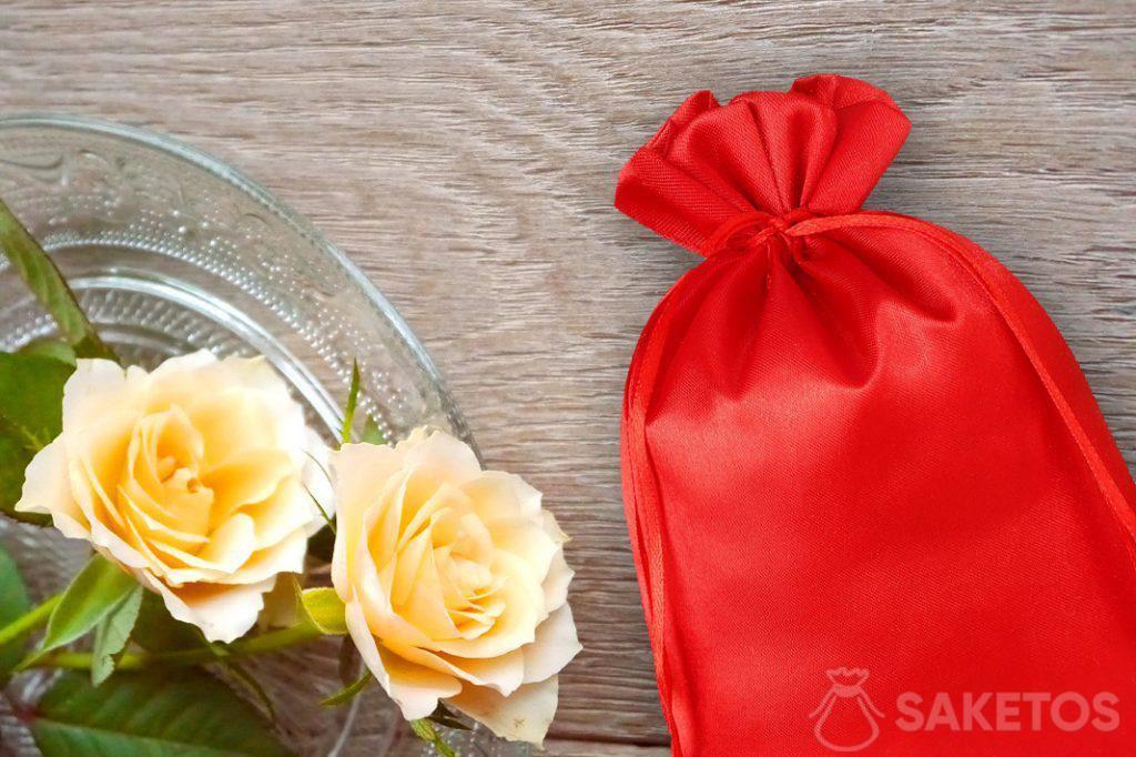 Roter Satinbeutel und Rosen