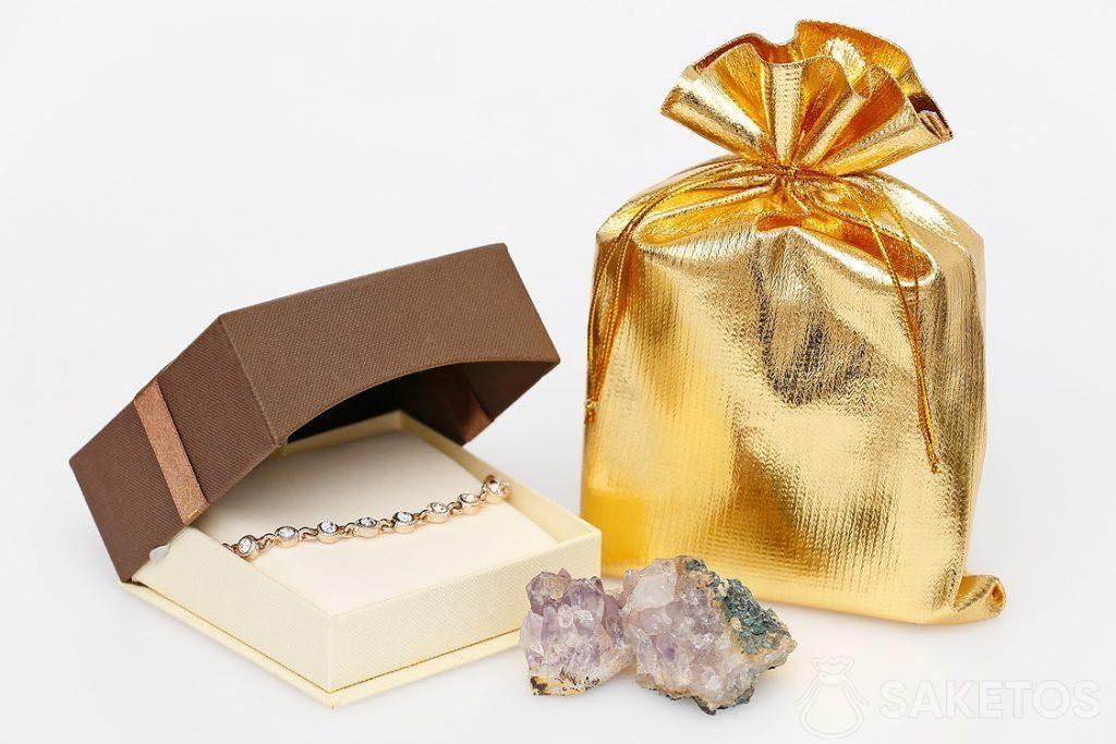 Goldenes metallisches Säckchen und ein elegantes Armband.