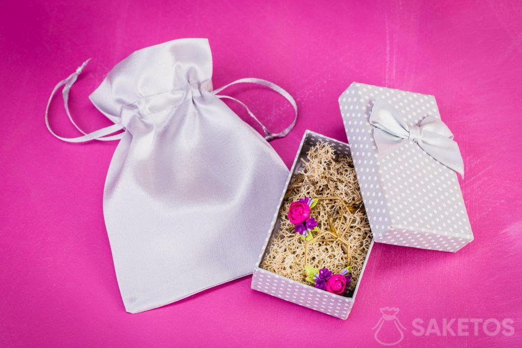 Silberner Satinbeutel als elegante Verpackung für eine Schmuckschatulle aus Pappe mit Ohrringen.