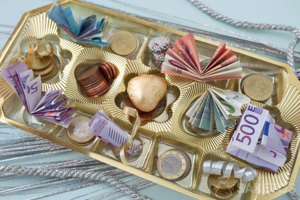 Banknoten und Münzgeld können in eine Pralinenschachtel hineingelegt werden