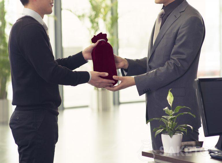 Alkoholflasche in Geschenkverpackung in einem Veloursbeutel