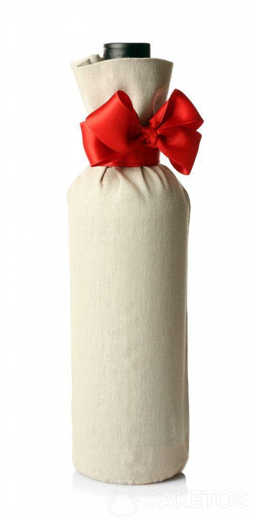 Alkoholflasche in Geschenkverpackung in einem Leinenbeutel mit roter Schleife