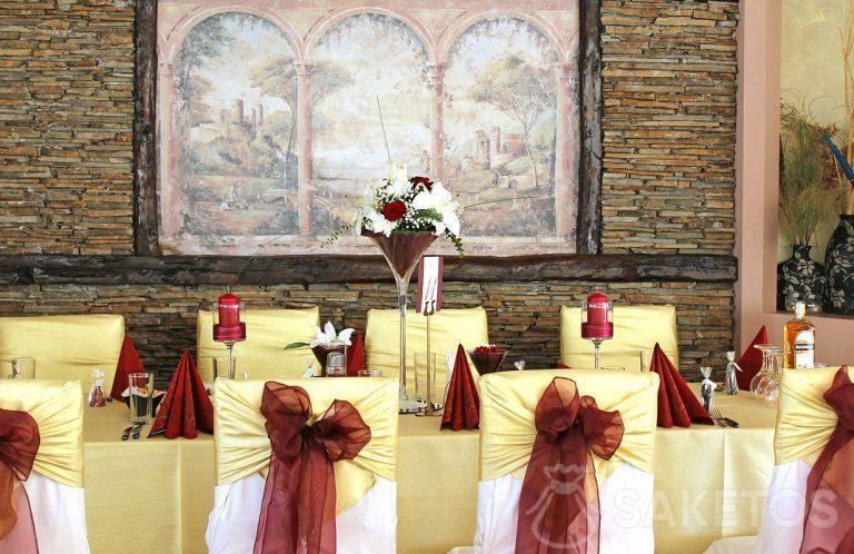 1.Dekoratives burgunderfarbenes Gedeck - eine Vase, Servietten, Kerzenhalter und Schleifen auf Stühlen