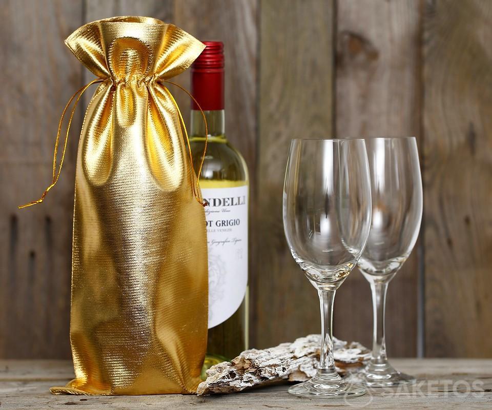 Eine Flasche Wein in einer goldmetallischen Tüte