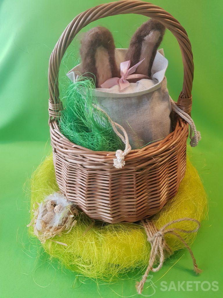 Ein Korb mit einer Leinentasche, aus der die Ohren aus Filzhasenwolle herausragen.