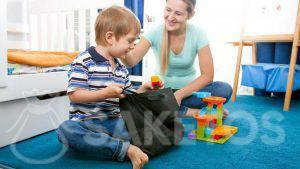 Ein Junge holt Bauklötze aus dem Stoffbeutel heraus.